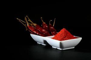 poudre froide avec du froid rouge dans une assiette blanche, piments séchés sur fond noir photo