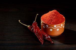 poudre froide dans un pot en argile avec des piments rouges frais et séchés sur fond de bois photo