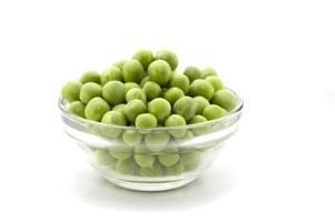 Pois verts frais dans le bol en verre isolé sur fond blanc photo