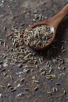 graines de cumin dans une cuillère en bois sur un fond texturé photo
