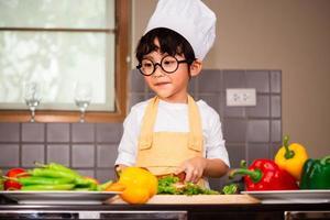 garçon asiatique faisant cuire des aliments et tenant une cuillère en bois photo