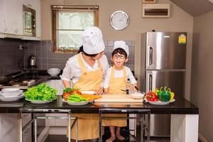 femme asiatique avec son fils la cuisson des aliments dans la cuisine à la maison photo