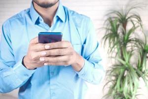 gros plan de la main du jeune homme à l'aide d'un téléphone intelligent. photo