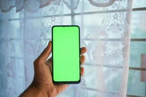 Close up of young man hand using smart phone avec écran vert photo