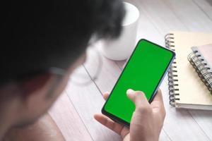 vue arrière de la main du jeune homme à l'aide d'un téléphone intelligent avec écran vert photo