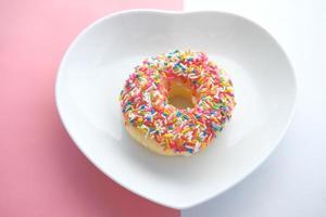 beignets colorés sur plaque en forme de coeur photo