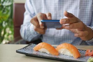 Jeune homme prenant une photo de saumon sushi nigiri japonais avec téléphone