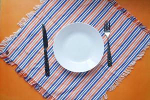 couverts et assiette vide sur fond de couleur de haut en bas photo