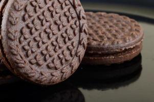 biscuits sandwich au chocolat brun avec garniture à la crème dans une assiette photo
