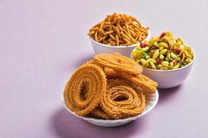 snack indien chakli, chakali ou murukku et farine de gramme besan sev et chivada ou chiwada sur fond rose. nourriture de diwali photo