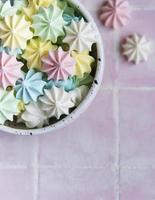 petites meringues colorées dans l'assiette en céramique photo