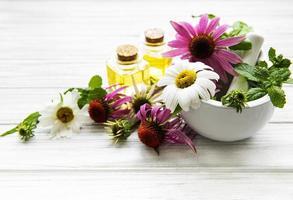 fleurs et plantes médicales en mortier et huiles essentielles sur une table en bois blanc photo