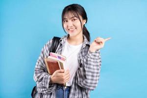 étudiante asiatique avec une expression ludique sur fond bleu photo