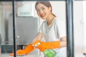 belle femme asiatique nettoyant le coin cuisine photo