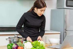 la femme apprend à cuisiner toute seule à la maison, cours de cuisine en ligne photo