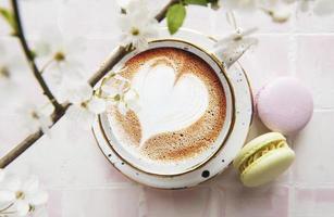 café avec un motif en forme de cœur et desserts macarons sucrés photo