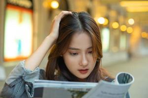 belle fille asiatique lisant un magazine dans la rue photo