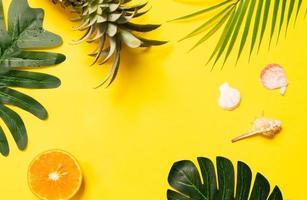 concept d'été avec coquillage, orange et feuille sur fond jaune photo