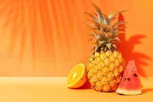 concept d'été avec fond orange, ananas et pastèque et orange photo