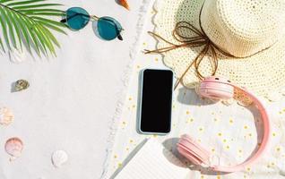 le téléphone et le casque sont posés sur le tapis sur le sable photo