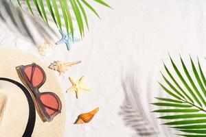 fond d'été avec coquillage, lunettes de soleil et chapeau sur le sable photo
