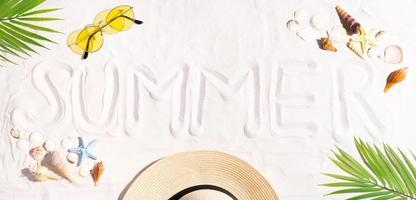 le mot été est écrit sur le sable photo