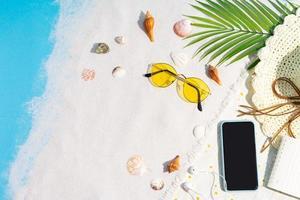 le téléphone est placé sur le sable avec des coquillages et des lunettes de soleil autour photo