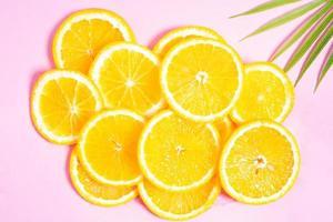 tranches d'orange placées sur un fond rose photo
