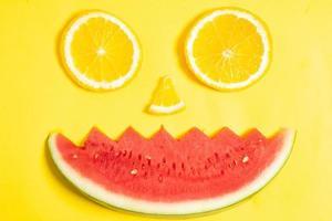tranches d'orange et morceaux de pastèque disposés en forme de visage humain photo