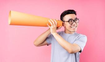 homme asiatique tenant un haut-parleur en papier sur fond rose photo