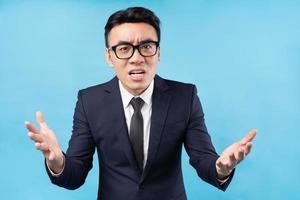 homme d'affaires asiatique portant un costume se sentant en colère sur fond bleu photo