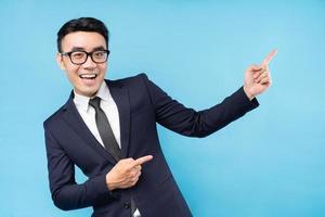 buisnessman asiatique portant costume pointant sur fond bleu photo
