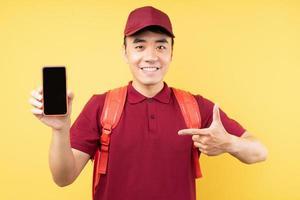 livreur asiatique portant un uniforme rouge posant sur fond jaune photo