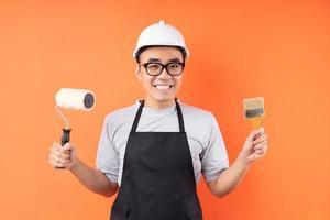 peintre asiatique tenant un pinceau posant sur fond orange photo