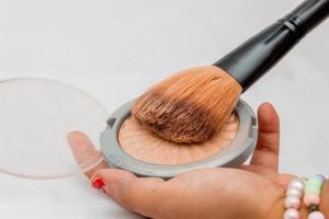 maquillage, poudre compacte avec pinceau sur une main blanche à rio de janeiro. photo