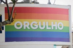 drapeau arc-en-ciel avec le mot fierté écrit en portugais sur la plage de copacabana à rio de janeiro. photo