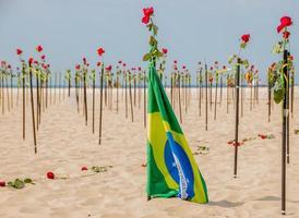 drapeau du brésil avec des roses en arrière-plan sur la plage de copacabana à rio de janeiro. photo