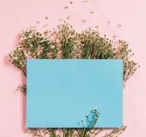 le papier bleu est placé sur un fond rose avec des fleurs autour de hoa photo