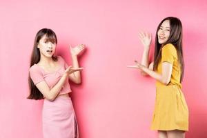 portrait de deux belles jeunes filles asiatiques posant sur fond rose photo