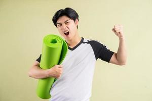 homme asiatique tenant un tapis de yoga sur fond vert photo