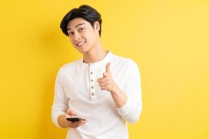 homme asiatique utilisant son téléphone et pointant vers l'extérieur sur fond jaune photo
