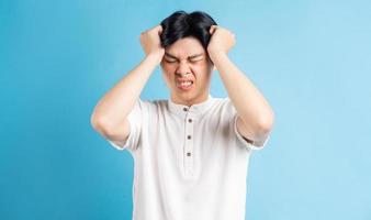 l'homme asiatique est agacé par un mal de tête photo
