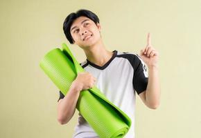 homme asiatique tenant un tapis de yoga sur fond bleu photo