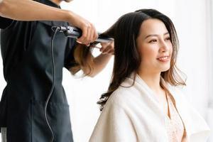 femme asiatique avec une expression heureuse faisant de la coiffure au salong photo