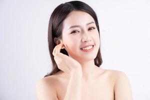 belle femme xing avec une peau fraîche souriante sur fond photo