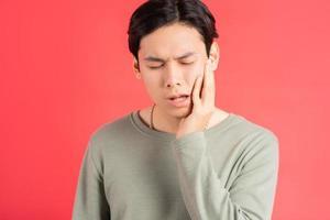une photo d'un bel homme asiatique souffrant de carie dentaire