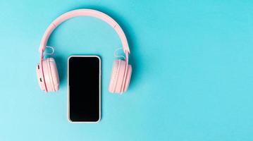 téléphone rose et écouteurs sur fond bleu photo