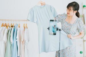 une belle jeune femme asiatique diffuse en direct pour vendre des vêtements sur des plateformes de réseaux sociaux et des sites de commerce électronique. ce sera la tendance future de l'industrie du commerce électronique photo