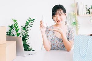 Une femme d'affaires asiatique utilise des smartphones pour diffuser en direct la vente de produits cosmétiques sur des sites de réseaux sociaux et des sites de commerce électronique. photo