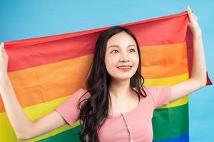 jeune femme asiatique tenant un drapeau arc-en-ciel pour soutenir la communauté lgbtq photo